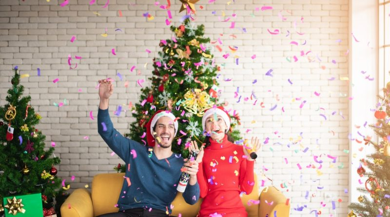 man-and-woman-wearing-santa-hats-sitting-on-sofa-popping-a-3183392
