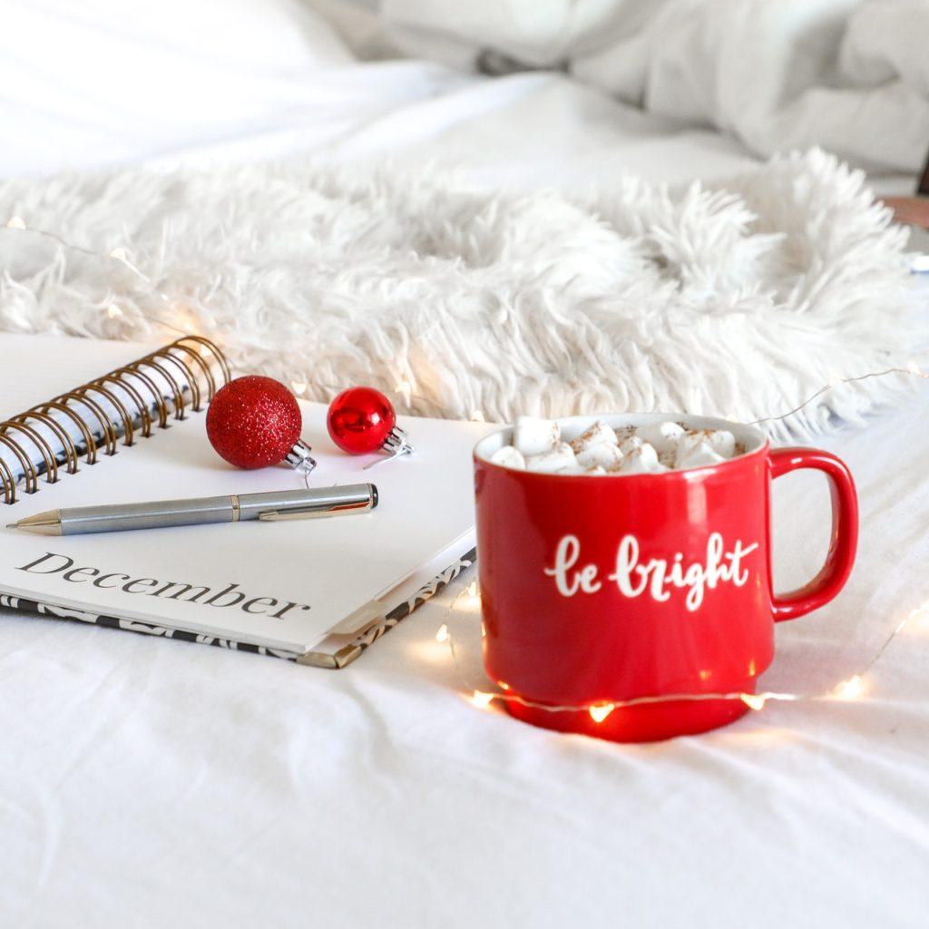red-ceramic-mug-on-white-mat-beside-notebook-1661961