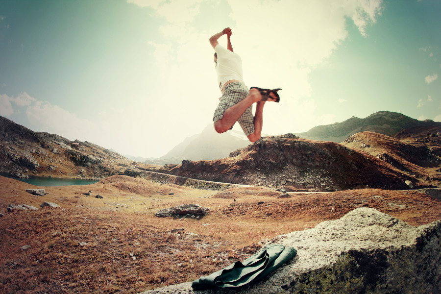 man jumping on landscape near mountains