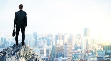 business-man-on-mountain-overseeing-city