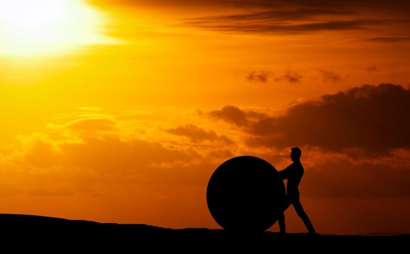 challenge-difficult-man rolling huge ball up hill