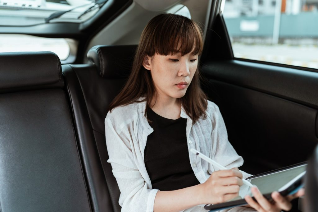 woman in car working on tablet